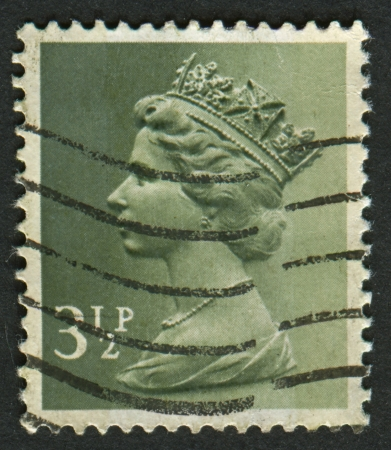 realms: UK-CIRCA 1971: A stamp printed in UK shows image of Elizabeth II is the constitutional monarch of 16 sovereign states known as the Commonwealth realms, in dull orange, circa 1971.