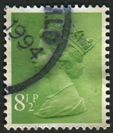 definitive: Reino Unido-alrededor de 1975: Un sello impreso en Reino Unido muestra imagen de Isabel II es el monarca constitucional de 16 estados soberanos conocidos como los reinos de la Commonwealth, en el verde amarillento, alrededor de 1975.