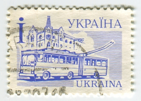 trackless: UKRAINE - CIRCA 2006: A stamp printed in Ukraine shows image of the A trolleybus (also known as trolley bus, trolley coach, trackless trolley, trackless tram or trolley is an electric bus that draws its electricity from overhead wires using spring-loaded  Editorial
