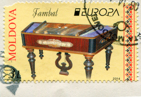 torn metal: GOMEL, BELARUS, APRIL 7, 2017. Stamp printed in Moldova shows image of  The cimbalom is a concert hammered dulcimer: a type of chordophone composed of a large, trapezoidal box with metal strings stretched across its top, circa 2014. Editorial
