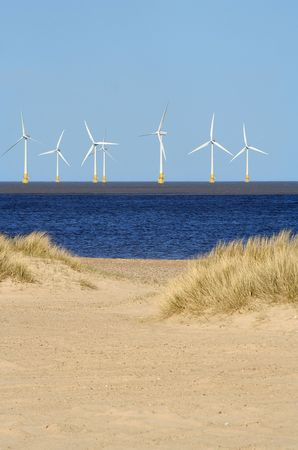 Beach and wind turbines at sea photo