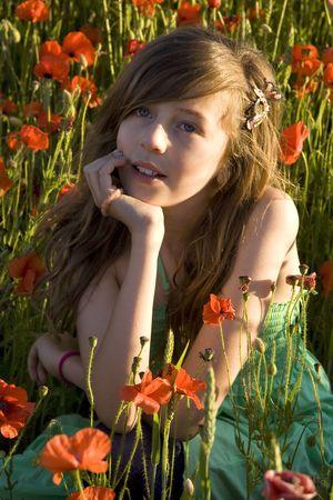 Girl in summer dress enjoying poppy field