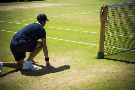 crouch: Tennis ballboy ready for action on sunny court