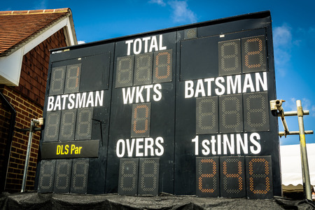 Electronic cricket scoreboard showing run chase in second innings Фото со стока