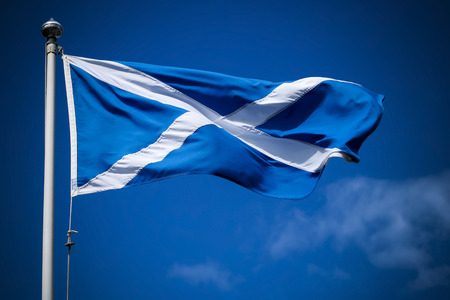 Scotland flag flying in sunshine against blue sky
