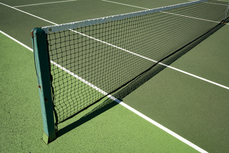Tennis net strung across artificial hardwearing tennis court