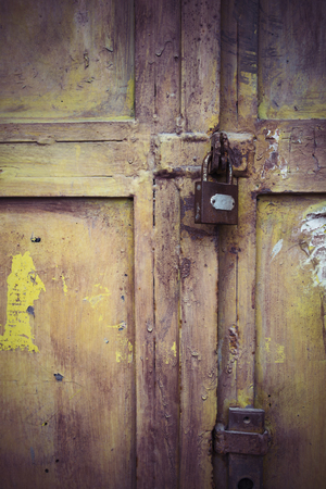 Weathered padlock and door with peeling paint Stock Photo