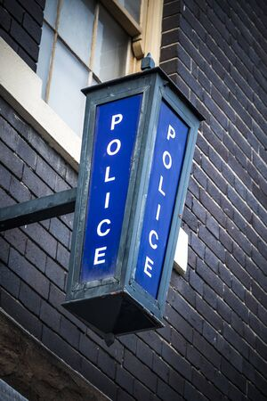 Police sign high on wall on exterior of police station