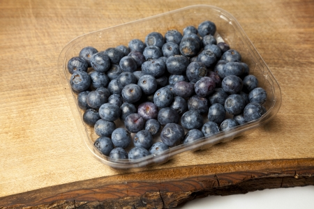 Punnet of blueberries on chopping board