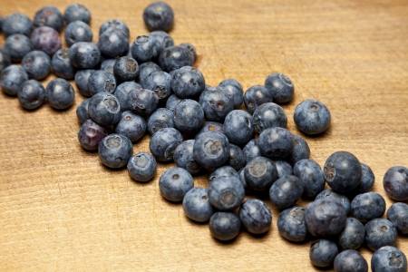 Diagonal line of blueberries on chopping board