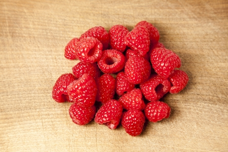 Bunch of raspberries on chopping board