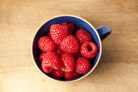 Cup of raspberries on chopping board