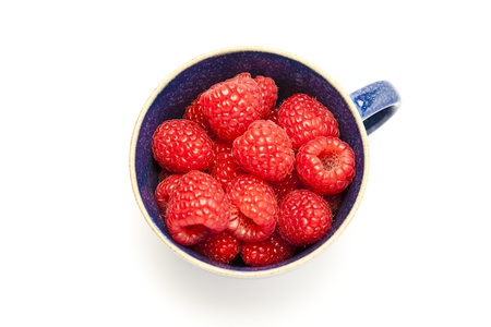 Cup of raspberries on white background