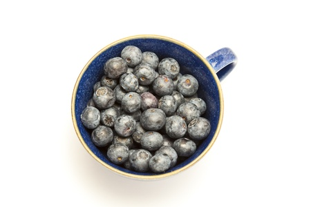 Cup of blueberries on white background