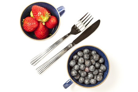 Cups of strawberries and blueberries on white background with copy space