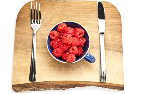 Cup of raspberries on a chopping board with cutlery Stock Photo