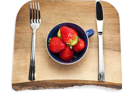 Cup of strawberries on a chopping board with cutlery Stock Photo