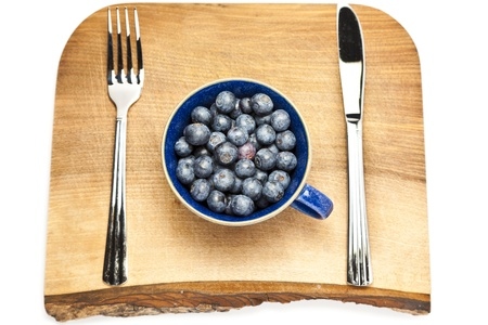Cup of blueberries on a chopping board with cutlery Stock Photo