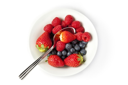Bowl of strawberries, blueberries and raspberries on a white background with copy space Stock Photo