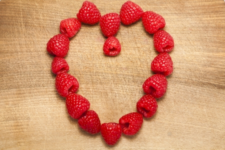 Bunch of raspberries arranged in a heart shape on a chopping board