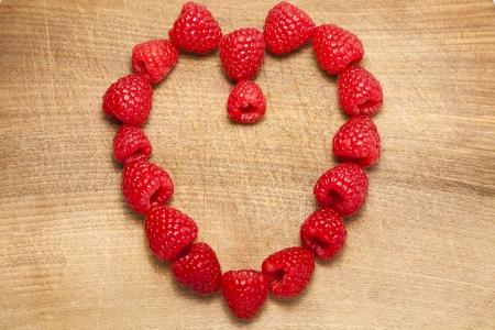 Bunch of raspberries arranged in a heart shape on a chopping board