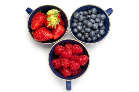 Cups of strawberries, blueberries and raspberries on a white background with copy space