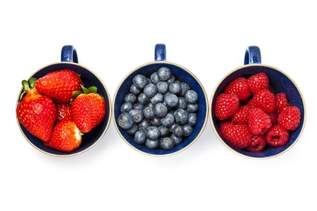 Cups of strawberries, blueberries and raspberries in a line on white background with copy space