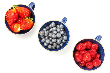 Cups of fruit on white background with copy space