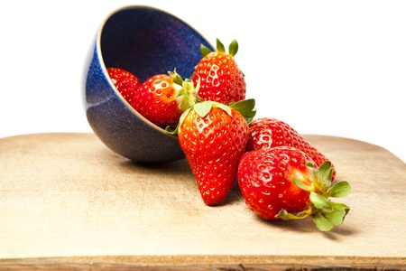 Strawberries spilling out of cup against white background with copy space
