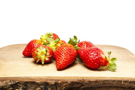 Bunch of strawberries on chopping board against white background with copy space Stock Photo
