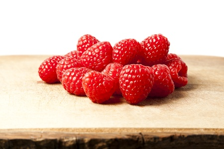 Bunch of raspberries on chopping board against white background with copy space