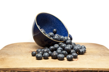 Blueberries spilling out of cup against white background with copy space