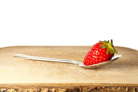 Strawberry on spoon against white background with copy space Stock Photo