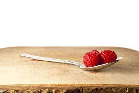 Raspberries on spoon against white background with copy space