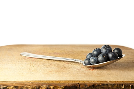 Blueberries on spoon against white background with copy space