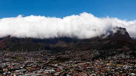 Table Mountain is a flat-topped mountain forming a prominent landmark overlooking the city of Cape Town in South Africa. It is a significant tourist attraction, with many visitors using the cableway or hiking to the top Stock Photo