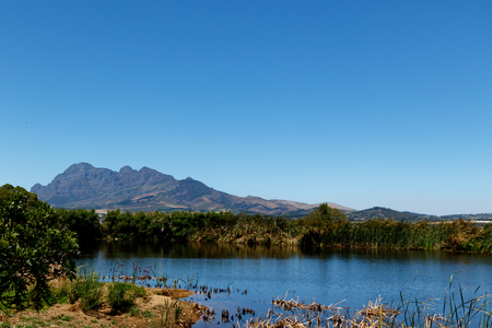 The dam, Bushes and Mountain View with Blue Skies.