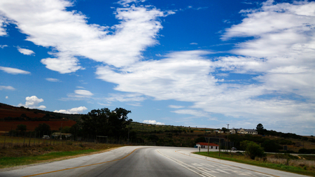 Clouds on the road with grass on the side. Stock Photo