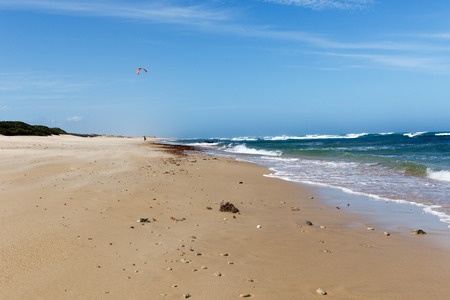 Walking on the sandy beach with a rough sea on the side. Stock Photo