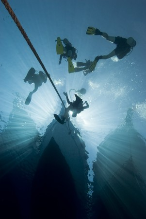 Silhouette shot of scuba divers at the bow of a dive boat. Red Sea, Egypt.