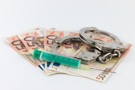 Drug-related crime, Handcuffs on money bills photo