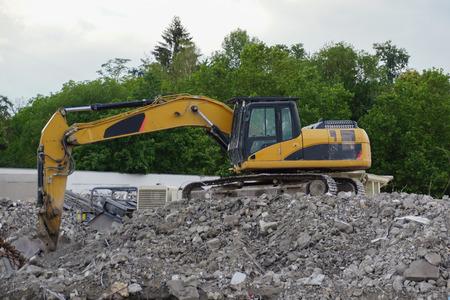 tailings: Yellow excavator at demolition on mountain of debris