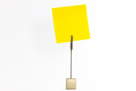 take down notice: Paperclip holds empty yellow square sticky note Stock Photo
