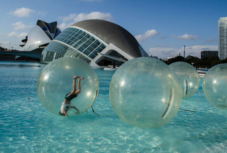VALENCIA, SPAIN - OCTOBER 9, 2016: A boy is somersaulting in a bubble floating in the water. In the background is the City of the Arts, Valencia, Spain. Editorial