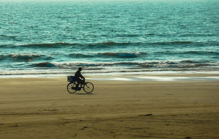 GOA, INDIA, MARCH 5, 2011: Silhouette of bicyclist that goes on the wave on the background of the waves of the Indian ocean Editorial