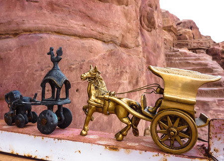 PETRA, JORDAN, NOV 25, 2011: Ancient horse and a copper chariot - souvenirs in Petra City against red rose rock formation