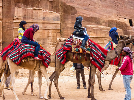 PETRA, JORDAN: Group of tourists riding camels, getting ready for the trip, beside are the drivers - bedouins. Camels covered with bright national coverlet, Petra (Rose City)
