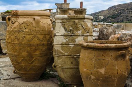 Creta, Grecia - noviembre de 2017: Primer - tres ánforas antiguas, en el fondo - ruinas escénicas del palacio de Minoan de Knossos