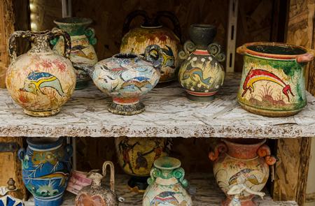 HERAKLION, GRECIA - noviembre de 2017: vasijas griegas pintadas y varias ánforas, hechas a mano, de pie en un estante en una tienda de recuerdos
