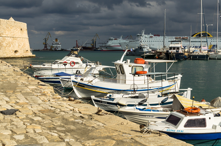 HERAKLION, GREECE - November, 2017: In the foreground: boats in bright sunlight, in the background cruise liners against a stormy sky near the old Venetian fortress Koule, Heraklion port, Crete Editorial